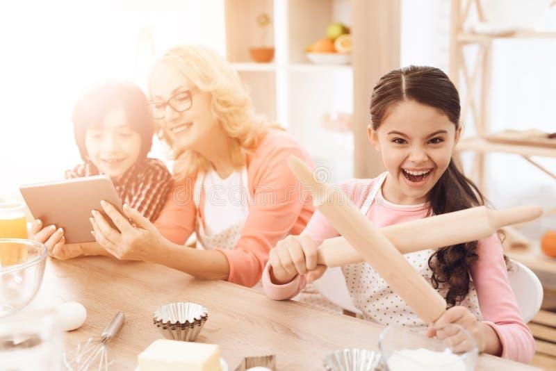 La niña sostiene los rodillos en sus manos, sentándose en cocina con su abuela y nieto foto de archivo libre de regalías