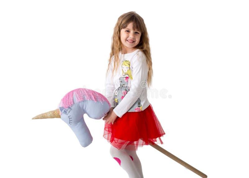 La niña sostiene un canto del juguete entre las piernas en un fondo blanco Aislado fotos de archivo