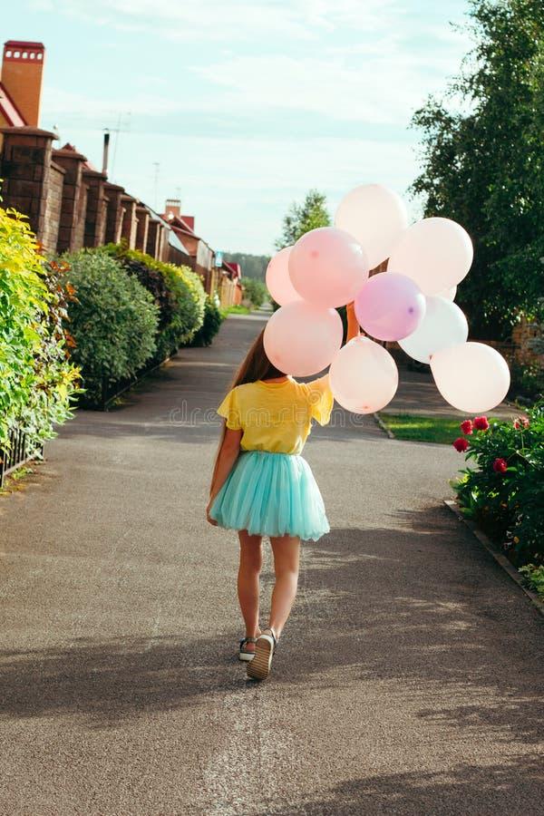 la niña sostiene un manojo de globos y de paseos abajo de la calle con ella de nuevo a imagen de archivo libre de regalías