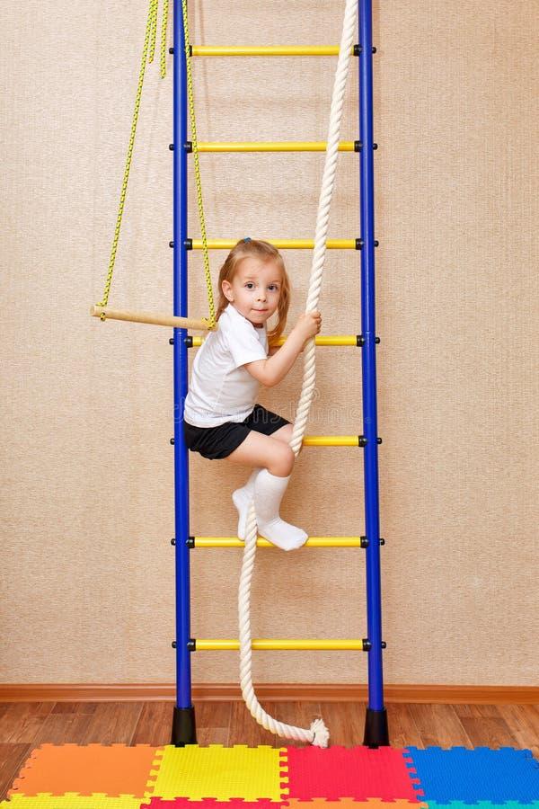 La niña sube las escaleras que se aferran para rope imagen de archivo