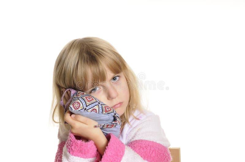 La niña tiene dolor de oídos imagen de archivo