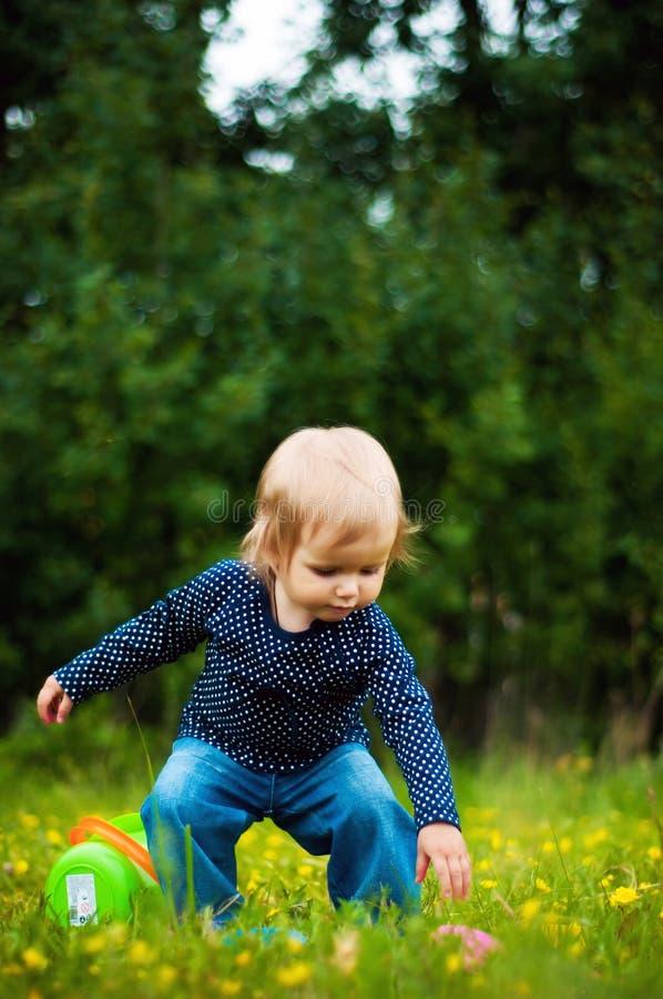 La niña toma un juguete caido imagen de archivo