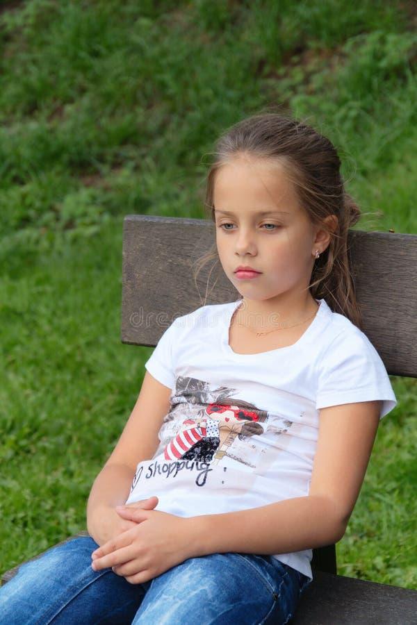 La niña triste piensa la mirada abajo, en banco imágenes de archivo libres de regalías