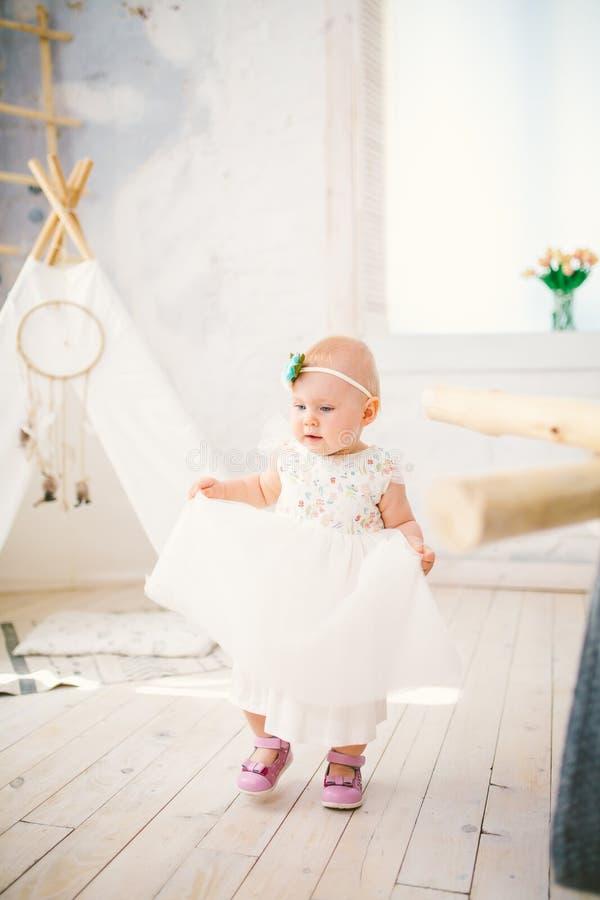 La niña un año con los ojos azules rubios en un vestido blanco enorme está contenta y juega en un cuarto brillante en fondo de un foto de archivo
