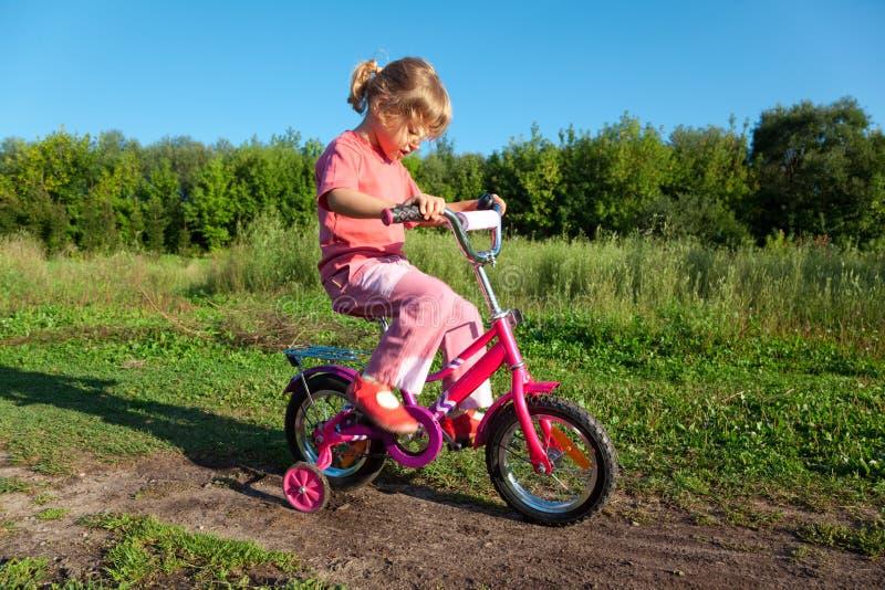 La niña va para el mecanismo impulsor en la bicicleta en parque imagen de archivo