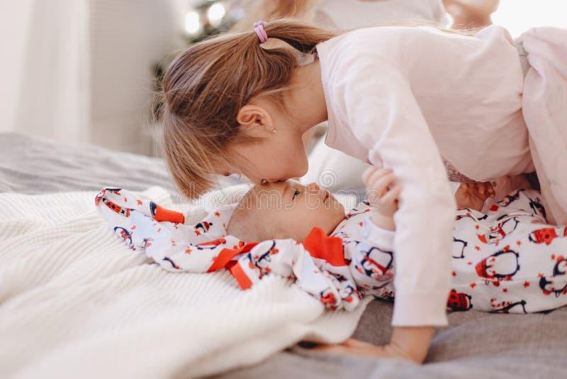 La niña vestida en pijama besa a su hermano minúsculo que miente en la cama fotografía de archivo