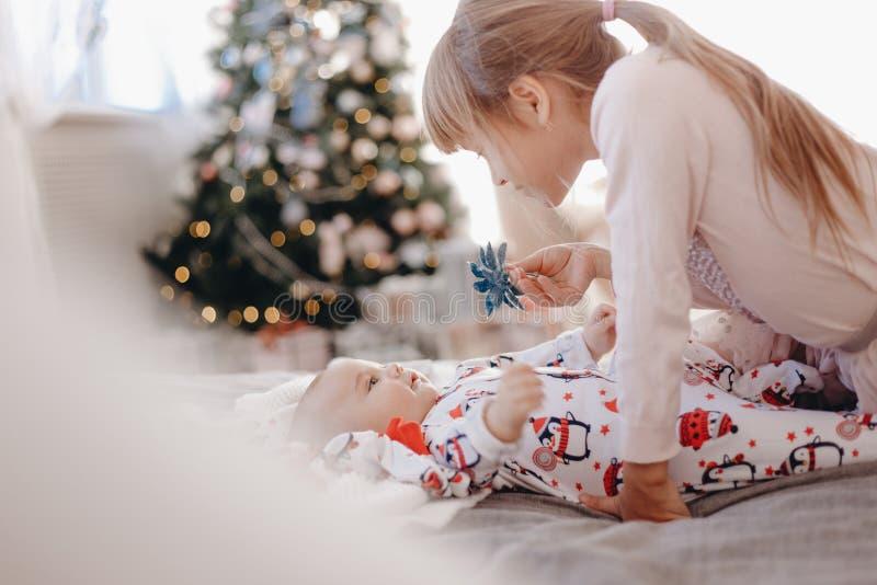 La niña vestida en pijama está mirando a su hermano minúsculo que miente en la cama en el cuarto acogedor con el árbol del Aà fotos de archivo libres de regalías