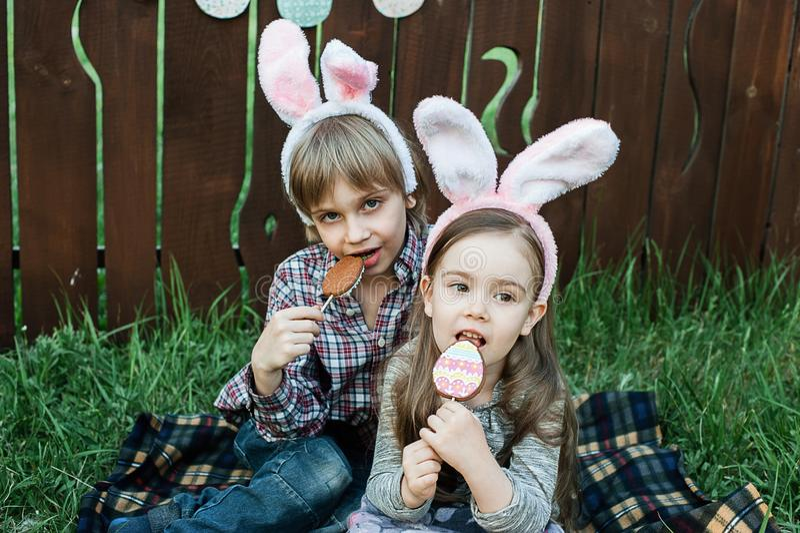 La niña y el muchacho comen una galleta del pan de jengibre en la forma del huevo de Pascua fotografía de archivo libre de regalías