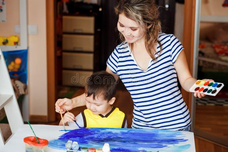 La niñez alegre, niño pequeño que juega con su madre, dibuja, las pinturas en las palmas Dibuje un mar imagen de archivo libre de regalías