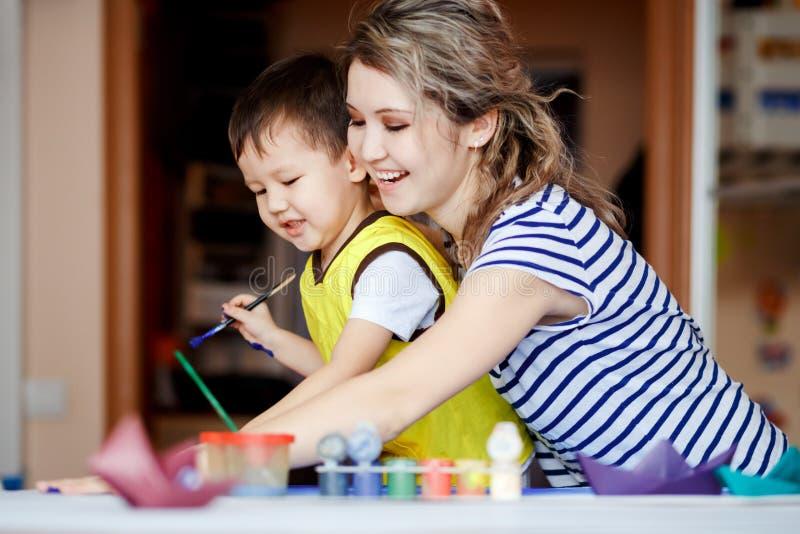 La niñez hilarante, niño pequeño que juega con su madre, dibuja, las pinturas en las palmas fotos de archivo