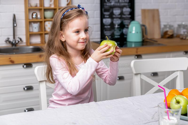 La ni?a feliz desayuna en una cocina blanca Ella come la manzana y la sonrisa Consumici?n sana imagen de archivo libre de regalías