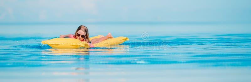 La ni?a linda disfruta de vacaciones en la piscina imagenes de archivo