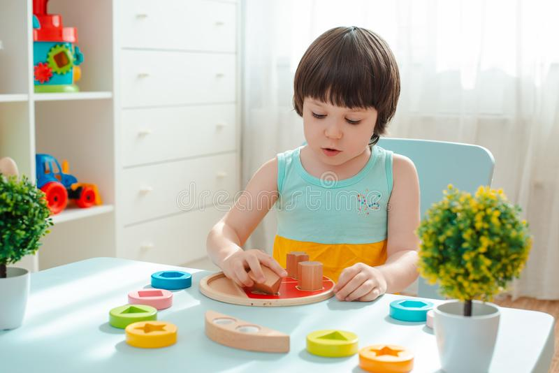 La ni?a recoge una pir?mide sin pintar de madera Los juguetes de los ni?os de madera naturales seguros fotografía de archivo libre de regalías