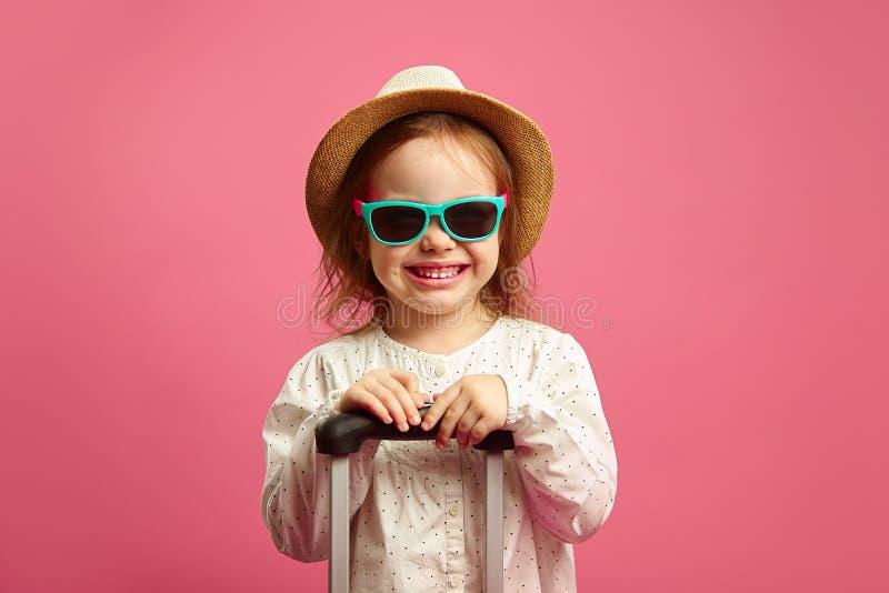 La ni?a sonriente en las gafas de sol y el sombrero de paja, sosteniendo la maleta en rosa aislado, expresa sinceramente alegr?a  fotografía de archivo