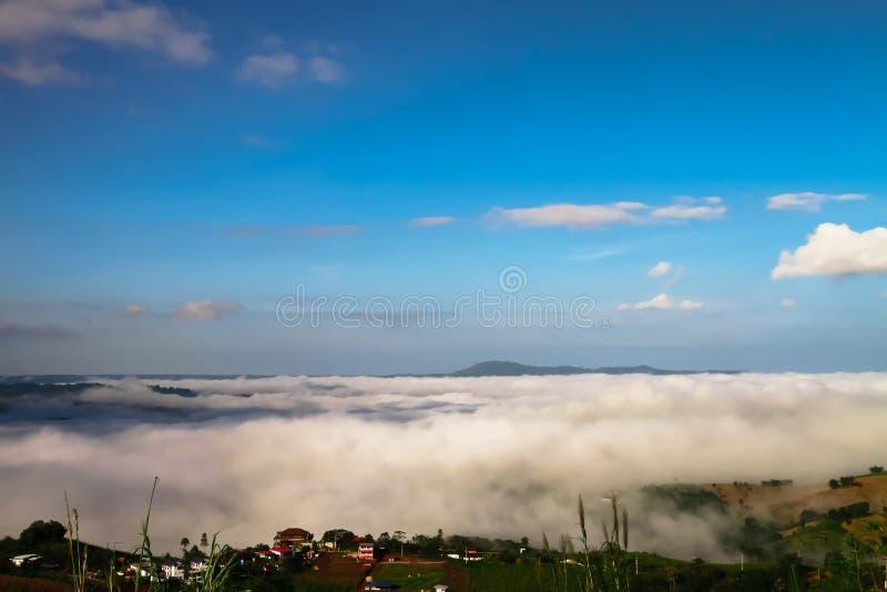 La niebla blanca golpea la sol de la mañana El pueblo de montaña cubrió w imagen de archivo
