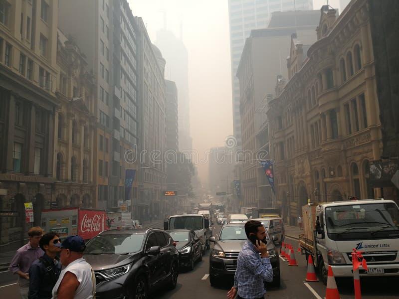 La niebla de humo cubrió los edificios de negocios de la ciudad a partir de un incendio de arbustos no controlado, causó el pluma imagen de archivo