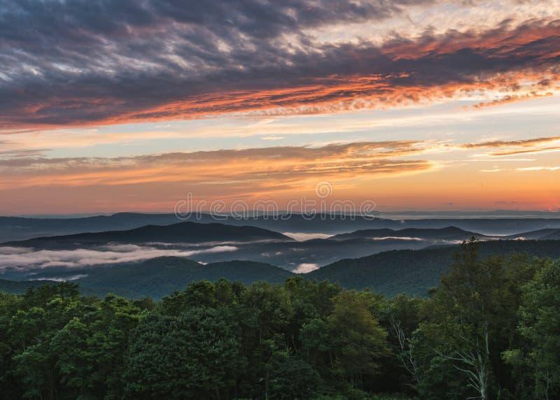 La niebla establece en el valle en la puesta del sol fotos de archivo