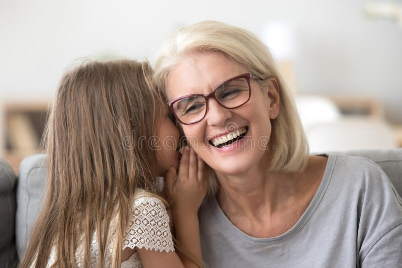 La nieta susurra algo a la abuelita que comparte secreto fotografía de archivo libre de regalías