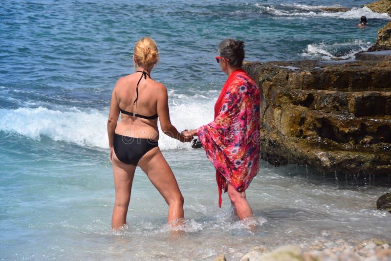 La nieta y la abuela que se colocan en el mar, gozan el tiempo caliente, el sol, el mar y compañía imágenes de archivo libres de regalías