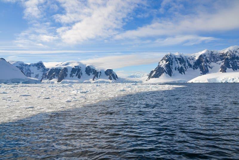 La nieve capsuló las montañas y el hielo quebrado en las aguas de la Antártida imágenes de archivo libres de regalías