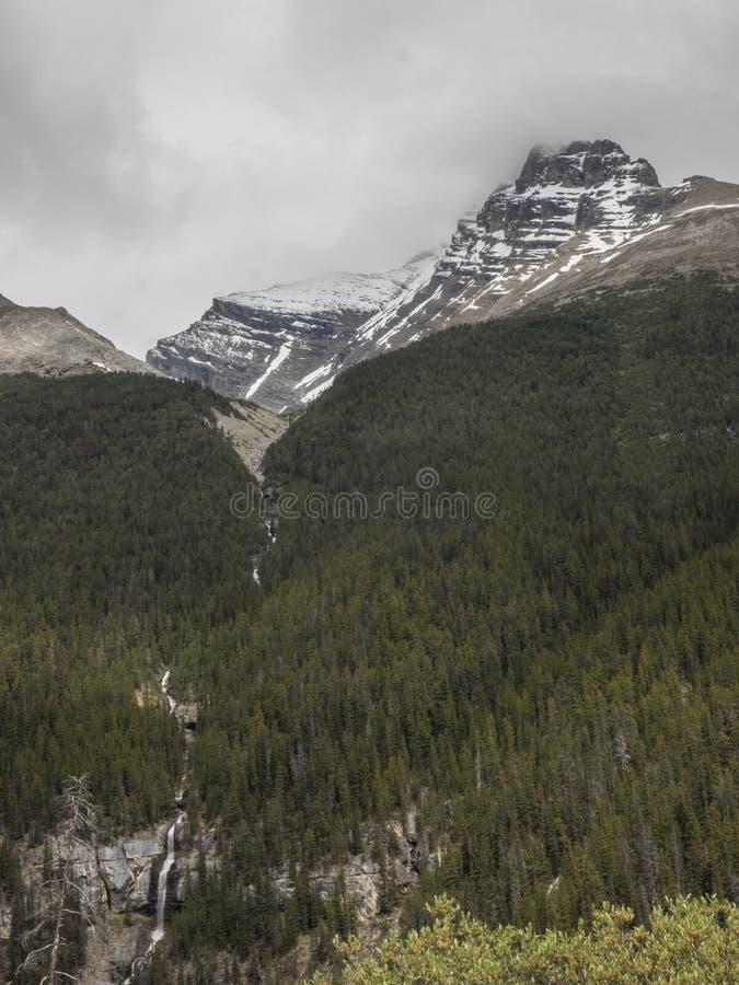 La nieve capsuló picos de montaña con las nubes de tormenta y las cascadas foto de archivo