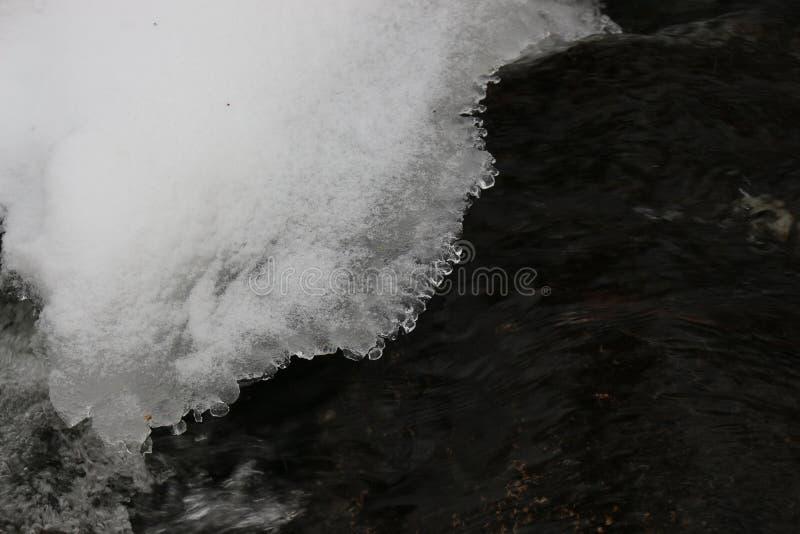 La nieve congelada cuelga sobre la agua corriente imagen de archivo