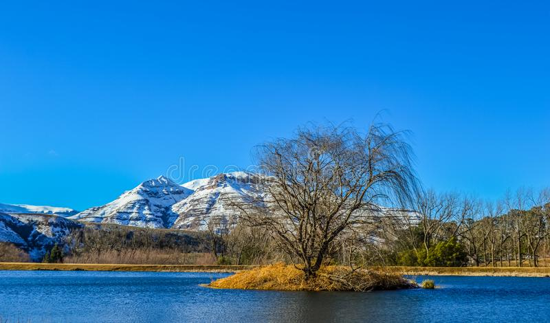 La nieve perfecta de la imagen capsuló las montañas de Drakensberg y los llanos verdes en Underberg cerca del paso Suráfrica de S fotos de archivo