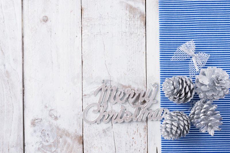 La nieve pintó conos del pino en la tabla de madera blanca rústica imagenes de archivo
