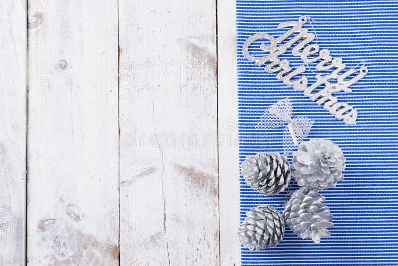 La nieve pintó conos del pino en la tabla de madera blanca rústica foto de archivo libre de regalías