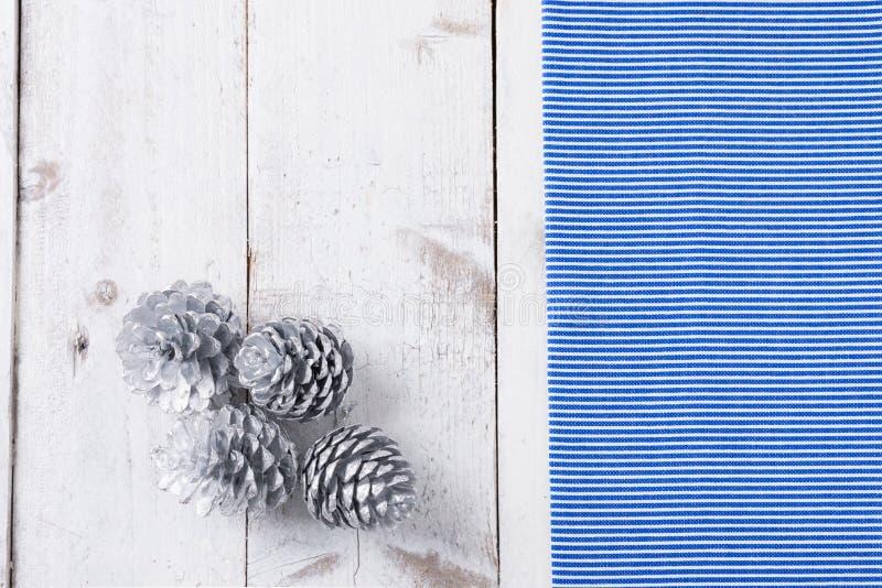 La nieve pintó conos del pino en la tabla de madera blanca rústica fotografía de archivo libre de regalías