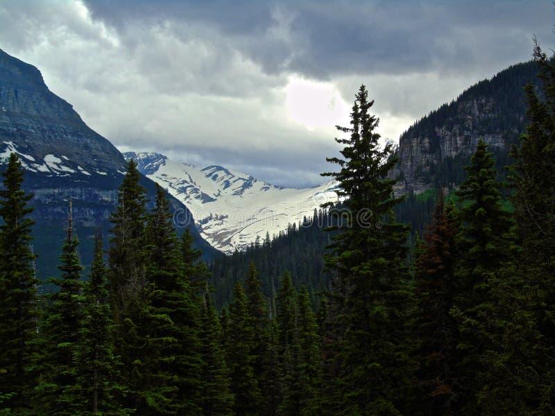 La nieve remató la montaña debajo del cielo enojado fotos de archivo