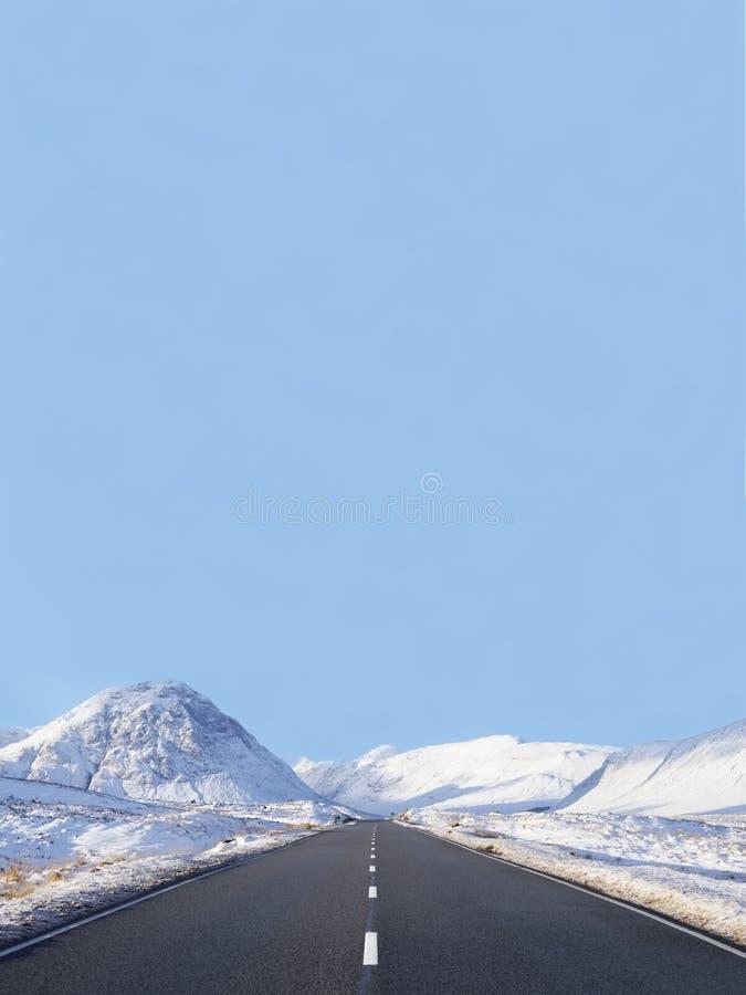La nieve vacía del horizonte del espacio en blanco del camino en los lados en montañas escocesas en Glencoe Rannoch amarra el cen fotos de archivo