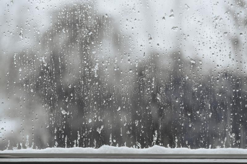 La nieve y la lluvia cae en una ventana, fondo del mún tiempo con el poli imagenes de archivo