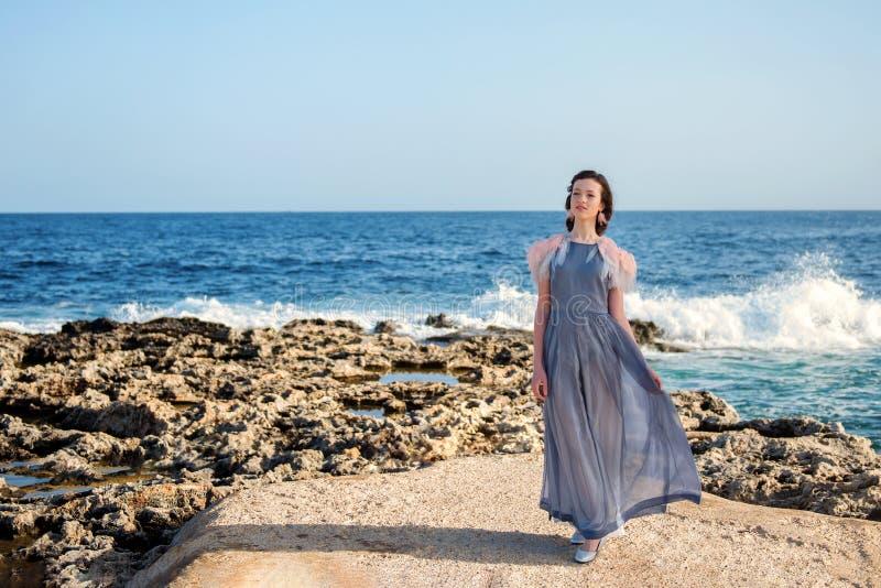 La ninfetta snella signorile in un vestito lungo fa un passo ordinatamente sulla riva della lava di un oceano infuriantesi blu co fotografia stock