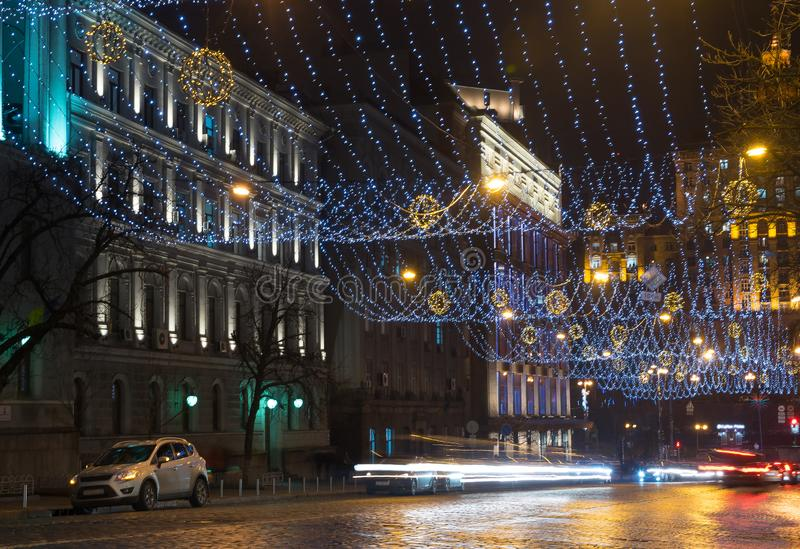 La noche en la ciudad grande, los coches que viajan en la carretera y brilla una luz que ciega Ciudad, Kiev - diciembre de 2017 fotos de archivo libres de regalías