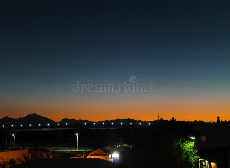 La noche en el desierto y una puesta del sol hermosa en las arenas son visibles solamente las luces en la distancia imagen de archivo libre de regalías