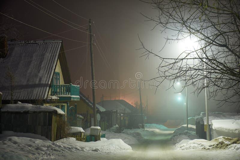 La noche tiró de la calle del país debajo de nieve en la estación del invierno fotografía de archivo