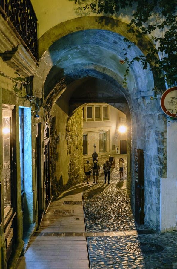 La noche tiró de un túnel en un estrecho, callejón solo con el suelo del guijarro con la gente irreconocible que daba un paseo y  imagen de archivo libre de regalías