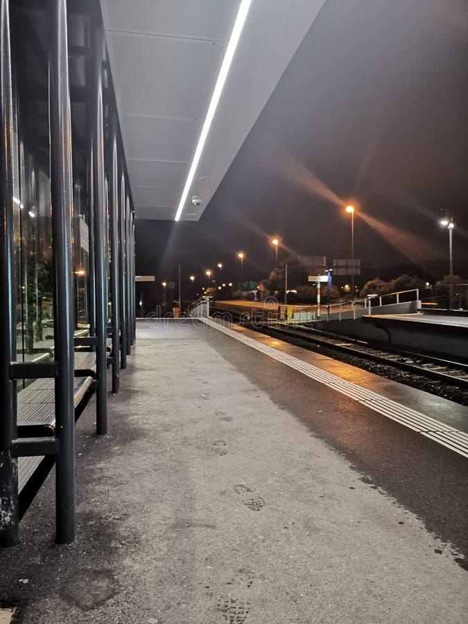 La noche tiró de una estación de metro en Suiza con algunas impresiones mojadas del pie en el piso fotos de archivo libres de regalías