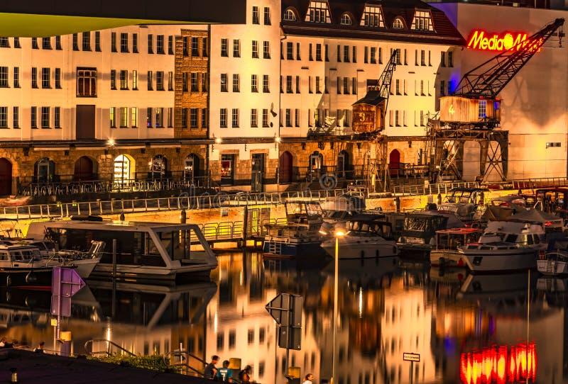 La noche tir? de un puerto en el canal de Teltow en Berl?n-Tempelhof con los barcos, los almacenes viejos y las gr?as Hay tambi?n fotos de archivo