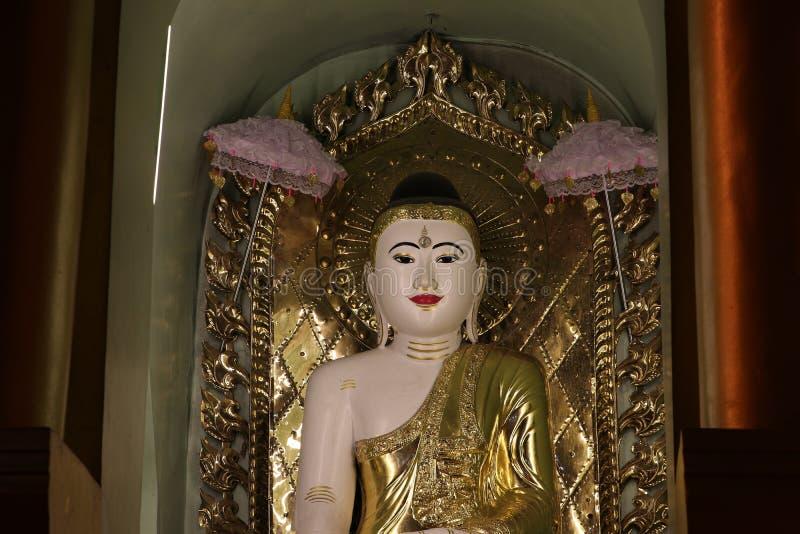 La noche tirada de la estatua de Buda del estuco adornada en de oro se engarce dentro del arco en la pagoda de Shwedagon, Rangún imágenes de archivo libres de regalías