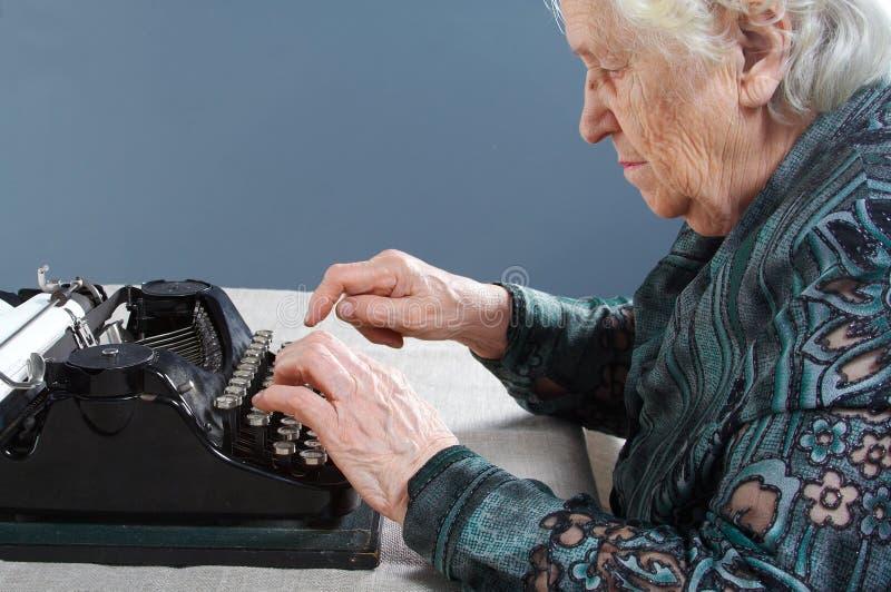 La nonna è una macchina da scrivere fotografie stock libere da diritti
