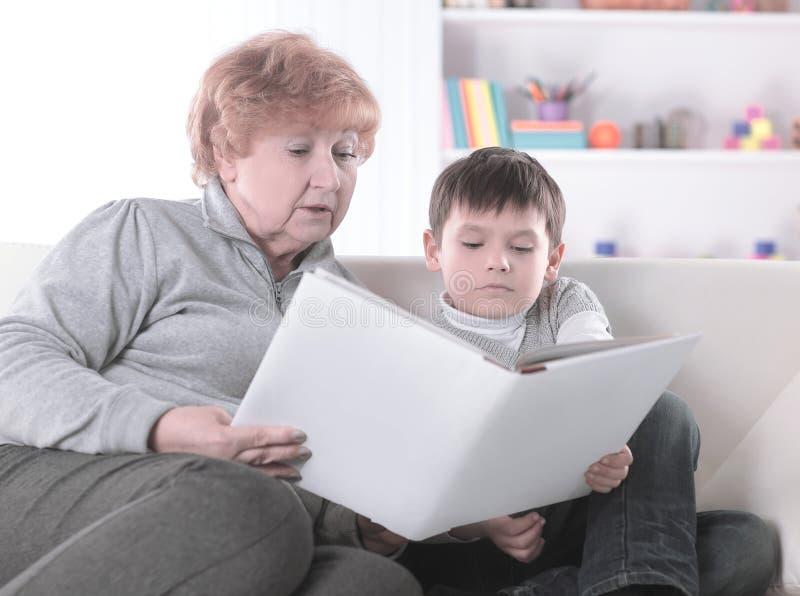 La nonna amorosa legge un libro al suo nipote Foto con lo spazio della copia immagine stock libera da diritti