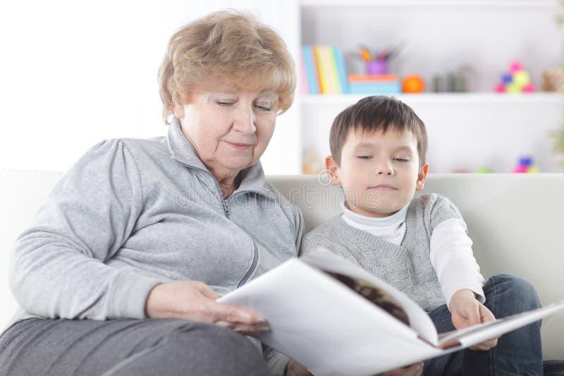 La nonna amorosa legge un libro al suo nipote Foto con lo spazio della copia immagini stock