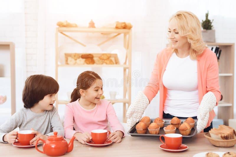 La nonna ben curato continua i muffin freschi della piattaforma per i piccoli nipoti dei bevitori immagine stock