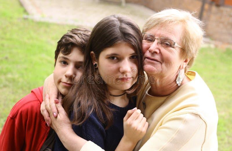 La nonna con i nipoti si chiude sulla foto dell'abbraccio fotografie stock libere da diritti