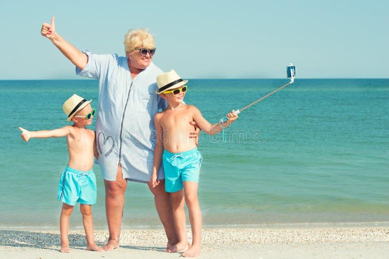 La nonna con i suoi nipoti sta riposando sul mare, essi è fa un selfie sulla spiaggia immagini stock