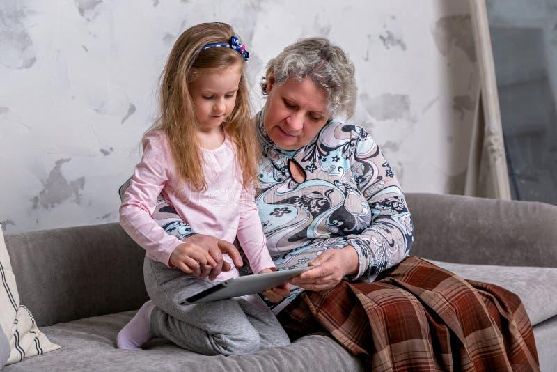 La nonna e la sua piccola nipote stanno guardando insieme i film e stanno giocando sul dispositivo mentre si sedevano sul sof? fotografia stock libera da diritti