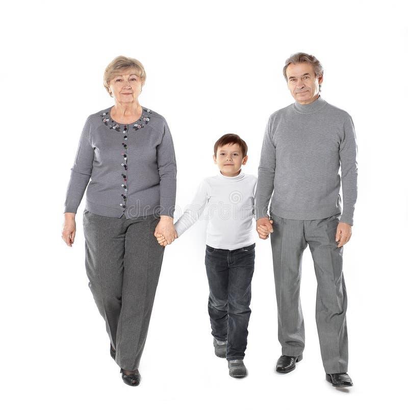 La nonna ed il nonno vanno con il suo nipote Isolato su priorit? bassa bianca fotografia stock libera da diritti