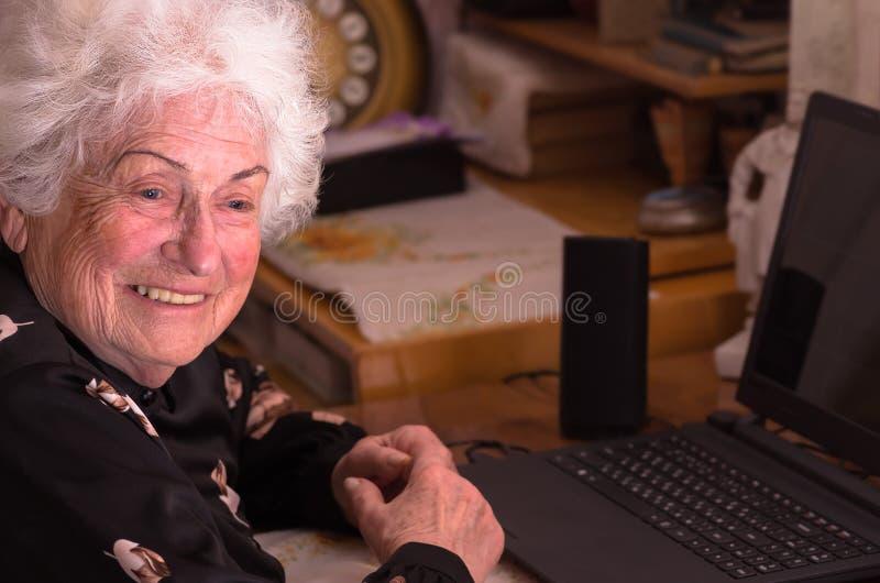 La nonna felice si siede al computer immagine stock
